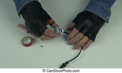 Man wearing black gloves fixing electrical plug