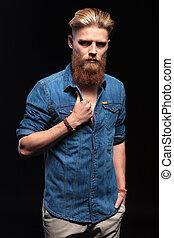 man wearing blue shirt pulling his collar