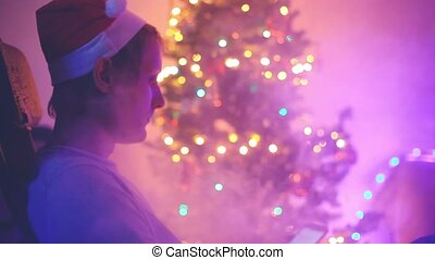 Man wearing christmas cap uses mobile phone on a Christmas tree lights bokeh background. 1920x1080