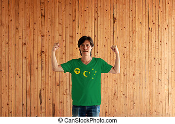 Man wearing Cocos (Keeling) Islands flag color of shirt and standing with raised both fist on the wooden wall background.