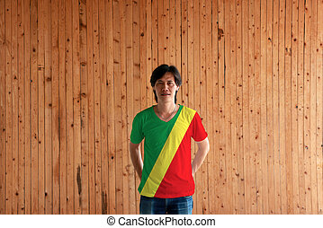 Man wearing Congo flag color of shirt and standing with crossed behind the back hands on the wooden wall background.