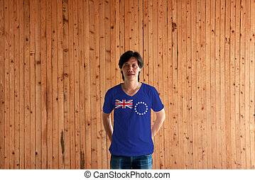 Man wearing Cook Islands flag color of shirt and standing with crossed behind the back hands on the wooden wall background.