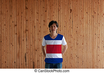 Man wearing Costa Rica flag color of shirt and standing with crossed behind the back hands on the wooden wall background.