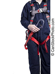 man wearing coveralls and fall protection harness and...