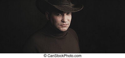 man wearing cowboy hat over black studio background
