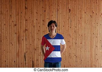 Man wearing Cuba flag color of shirt and standing with crossed behind the back hands on the wooden wall background.