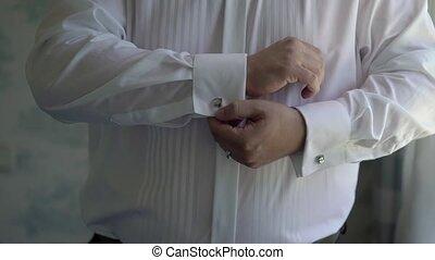 Man wearing cufflinks on white shirt closeup