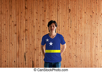 Man wearing Curacao flag color of shirt and standing with crossed behind the back hands on the wooden wall background.