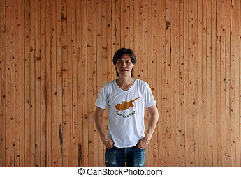Man wearing Cyprus flag color shirt and standing with two hands in pant pockets on the wooden wall background.
