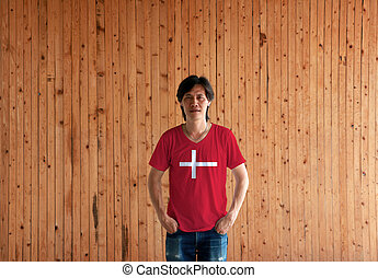 Man wearing Denmark flag color shirt and standing with two hands in pant pockets on the wooden wall background.