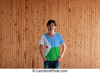 Man wearing Djibouti flag color shirt and standing with two hands in pant pockets on the wooden wall background.