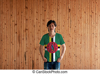 Man wearing Dominica flag color shirt and standing with two hands in pant pockets on the wooden wall background.