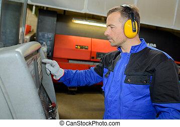 Man wearing ear protectors using machine
