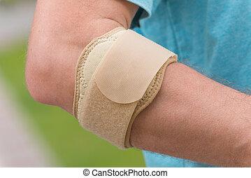 Man wearing elbow brace to reduce pain