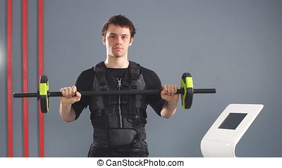 Man wearing EMS costume working out with barbell.