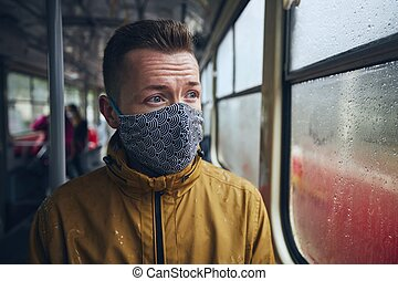Man wearing face mask in public transportation. Themes ...