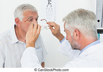 Man wearing glasses after taking vision test at doctor -...