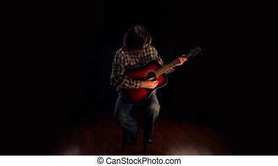 Man wearing glasses sits on chair and plays guitar at dark