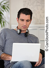 Man wearing headphones while using a laptop computer