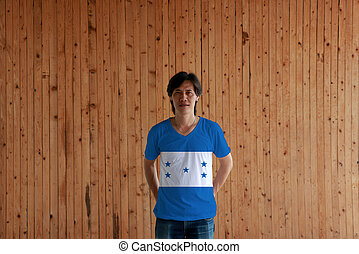 Man wearing Honduras flag color of shirt and standing with crossed behind the back hands on the wooden wall background.