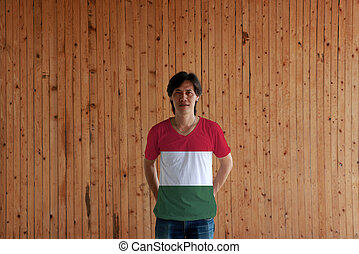 Man wearing Hungary flag color of shirt and standing with crossed behind the back hands on the wooden wall background.