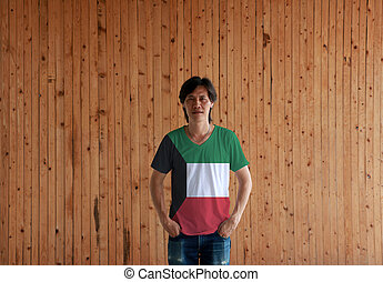Man wearing Kuwait flag color shirt and standing with two hands in pant pockets on the wooden wall background.