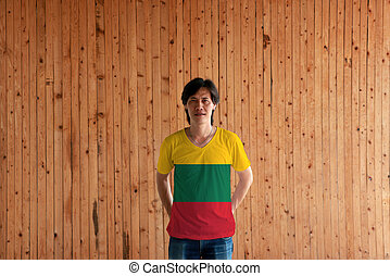 Man wearing Lithuania flag color of shirt and standing with crossed behind the back hands on the wooden wall background.