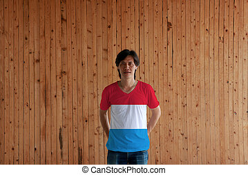 Man wearing Luxembourg flag color of shirt and standing with crossed behind the back hands on the wooden wall background.