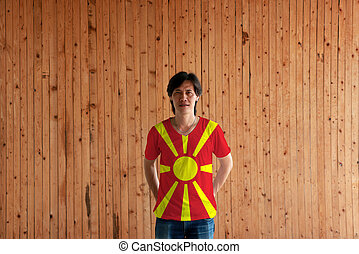 Man wearing Macedonia flag color of shirt and standing with crossed behind the back hands on the wooden wall background.