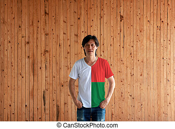 Man wearing Madagascar flag color shirt and standing with two hands in pant pockets on the wooden wall background.