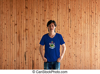 Man wearing Maine flag color shirt and standing with two hands in pant pockets on the wooden wall background.
