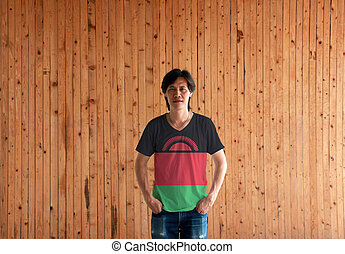 Man wearing Malawi flag color shirt and standing with two hands in pant pockets on the wooden wall background.