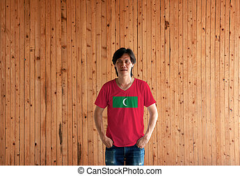 Man wearing Maldives flag color shirt and standing with two hands in pant pockets on the wooden wall background.