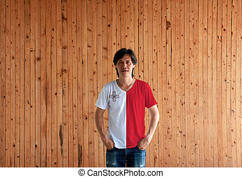 Man wearing Malta flag color shirt and standing with two hands in pant pockets on the wooden wall background.