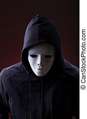 Man wearing mask - Man in hood wearing mask over dark...