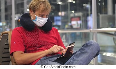 Health protection in public. Man wearing medical face mask at the airport to prevent coronavirus infection during world epidemic