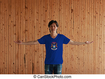 Man wearing Michigan flag color shirt and standing with arms wide open on the wooden wall background. State coat of arms on a dark blue field.