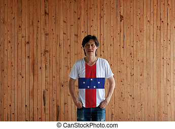 Man wearing Netherlands Antilles flag color shirt and standing with two hands in pant pockets on the wooden wall background,