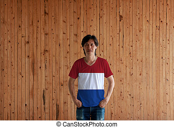 Man wearing Netherlands flag color shirt and standing with two hands in pant pockets on the wooden wall background.