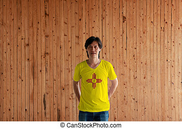 Man wearing New Mexico flag color of shirt and standing with crossed behind the back hands on the wooden wall background.
