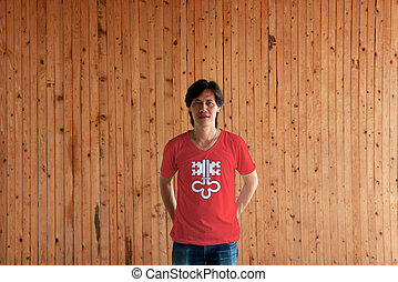 Man wearing Nidwalden flag color of shirt and standing with crossed behind the back hands on the wooden wall background.