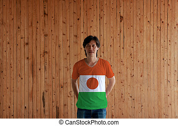 Man wearing Niger flag color of shirt and standing with crossed behind the back hands on the wooden wall background.