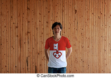 Man wearing Obwalden flag color of shirt and standing with crossed behind the back hands on the wooden wall background.