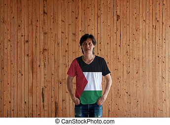 Man wearing Palestine flag color shirt and standing with two hands in pant pockets on the wooden wall background.