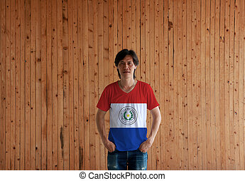 Man wearing Paraguay flag color shirt and standing with two hands in pant pockets on the wooden wall background.