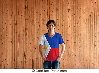 Man wearing Philippines flag color shirt and standing with two hands in pant pockets on the wooden wall background.