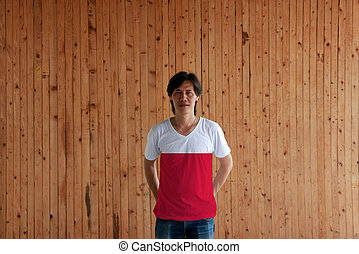 Man wearing Poland flag color of shirt and standing with crossed behind the back hands on the wooden wall background.