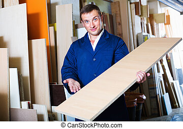Smiling diligent man wearing protective workwear standing with plywood in store