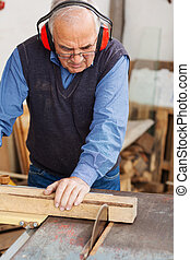 Man Wearing Red Ear Protectors While Using Table Saw