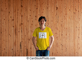 Man wearing Rhode Island flag color shirt and standing with two hands in pant pockets on the wooden wall background.